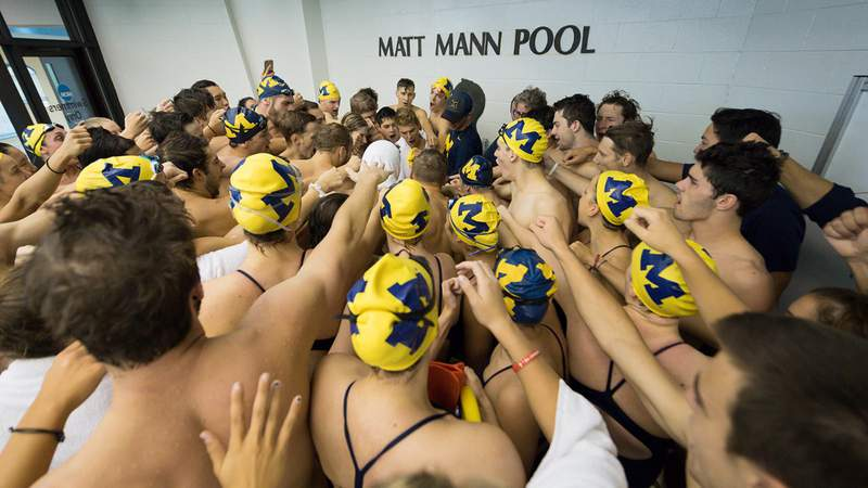 Members of the men's and women's swimming teams at the University of Michigan in a team huddle at Matt Mann Pool in Ann Arbor.