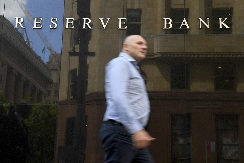 A man walks past the Reserve Bank of Australia headquarters in Sydney, Tuesday, Nov. 3, 2020. Australias central bank on Tuesday cut its benchmark interest rate by 0.15 of a percentage point to a record low 0.10% in a bid to lift the economy from a pandemic-induced recession.(Dan Himbrechts/AAP Image)
