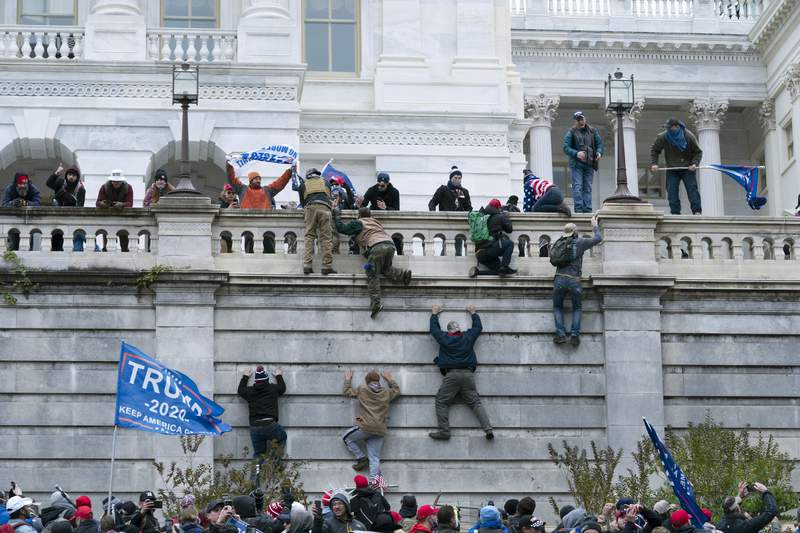 FILE - In this Jan. 6, 2021 file photo, violent insurrectionists loyal to President Donald Trump  scale the west wall of the the U.S. Capitol in Washington. Many of those who stormed the Capitol on Jan. 6 cited falsehoods about the election, and now some of them are hoping their gullibility helps them in court. Attorneys for several defendants facing charges connected to the deadly insurrection say they will raise their client's belief in conspiracy theories and misinformation, either as an explanation for why they did what they did, or as an attempt to create a little sympathy. (AP Photo/Jose Luis Magana, File)