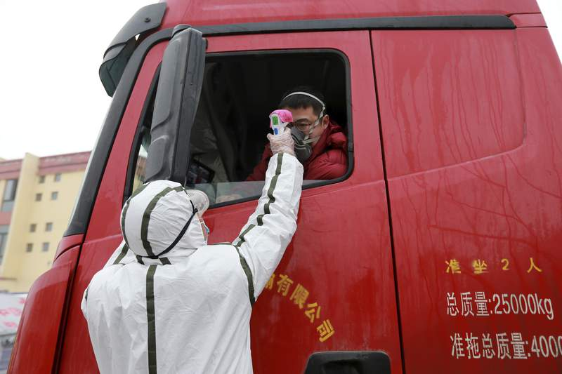 A worker in a hazardous materials suit takes the temperature of a truck driver at a checkpoint in Huaibei in central China's Anhui Province, Monday, Jan. 27, 2020. China on Monday expanded sweeping efforts to contain a viral disease by extending the Lunar New Year holiday to keep the public at home and avoid spreading infection as the death toll rose to 80. (Chinatopix via AP)