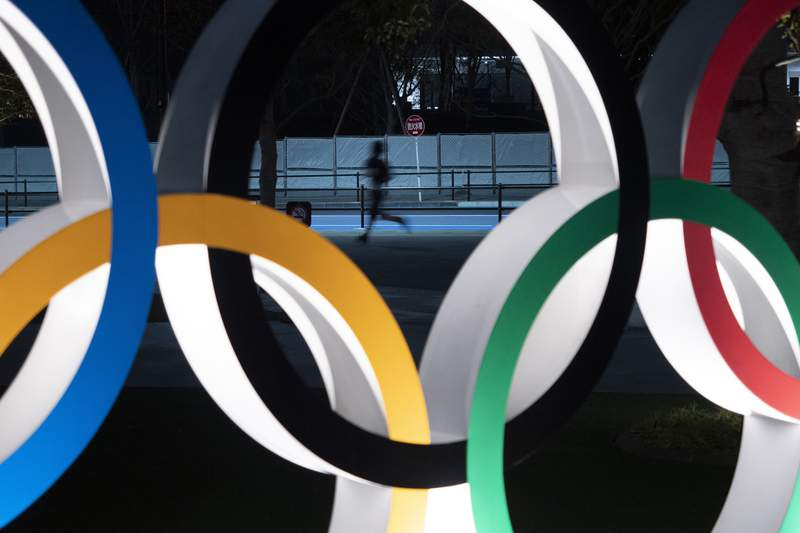 FILE - In this March 30, 2020, file photo, a man jogs past the Olympic rings in Tokyo. Former Olympic minister Toshiaki Endo said at a meeting of the ruling Liberal Democratic Party on Friday, June 5, 2020, that a decision of whether to hold the Games should be made around March, which is a crucial time to finalize participating athletes, NHK said. (AP Photo/Jae C. Hong, File)