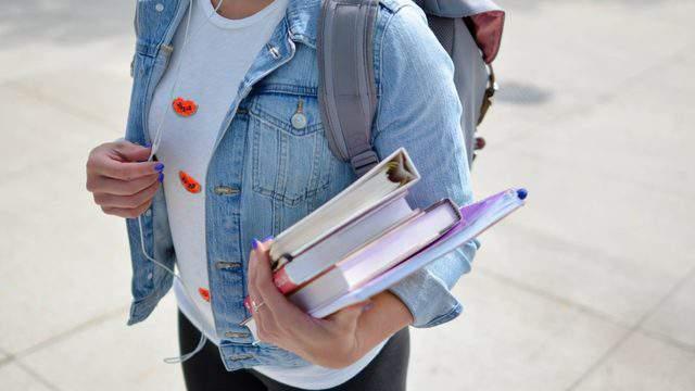 A high school student carrying books (Pixlr)