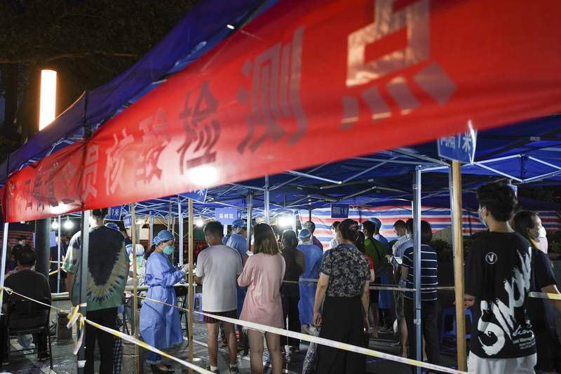 In this photo released by China's Xinhua News Agency, people line up for COVID-19 tests at a testing station in Nanjing in eastern China's Jiangsu Province, Wednesday, July 28, 2021. Roadblocks were set up to check drivers and a disease-control official called Thursday for increased testing of workers at Chinese ports after a rash of coronavirus cases traced to a major airport rattled authorities who thought they had the disease under control. (Li Bo/Xinhua via AP)