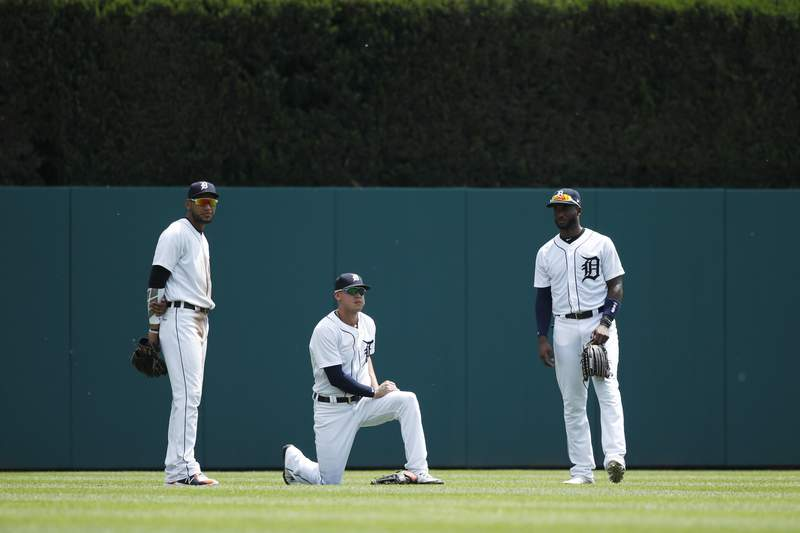 Victor Reyes #22, JaCoby Jones #21 and Niko Goodrum #28 of the Detroit Tigers look on during a pitching change in a game against the Los Angeles Angels at Comerica Park on May 31, 2018 in Detroit, Michigan. The Tigers won 6-2.