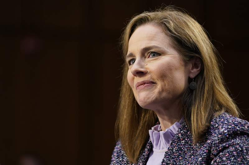 FILE - In this Oct. 14, 2020 file photo, Supreme Court nominee Amy Coney Barrett speaks during a confirmation hearing before the Senate Judiciary Committee, on Capitol Hill in Washington.  Supreme Court justice Amy Coney Barrett has delivered her first opinion.  The 7-2 decision released Thursday is in a case about the federal Freedom of Information Act, which Barrett explains makes records available to the public upon request, unless those records fall within one of nine exemptions. Barrett wrote for the court that certain draft documents do not have to be disclosed under FOIA.  The 11-page opinion comes in the first case Barrett heard after joining the court in late October following the death of Justice Ruth Bader Ginsburg.  Justice Stephen Breyer and Justice Sonia Sotomayor dissented. (AP Photo/Susan Walsh, Pool)