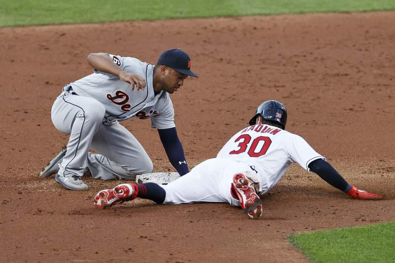 Cleveland Indians' Tyler Naquin (30) slides safely into second base with a one-run double as Detroit Tigers' Jonathan Schoop, left, covers during the second inning of a baseball game, Friday, Aug. 21, 2020, in Cleveland. (AP Photo/Ron Schwane)