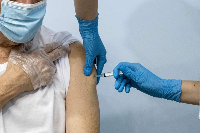 FILE - In this Jan. 20, 2021, file photo, a Russian medical worker, right, administers a shot of Russia's Sputnik V coronavirus vaccine to a patient in a vaccination center in Moscow, Russia. (AP Photo/Pavel Golovkin, File)