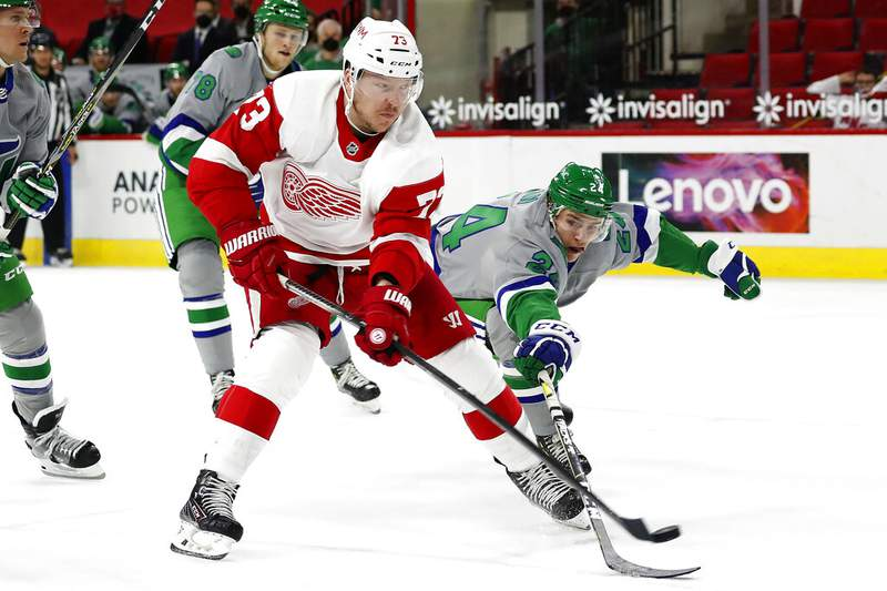 Detroit Red Wings' Adam Erne (73) lifts the puck over the stick of Carolina Hurricanes' Jake Bean (24) to score a goal during the third period of an NHL hockey game in Raleigh, N.C., Saturday, April 10, 2021. (AP Photo/Karl B DeBlaker)