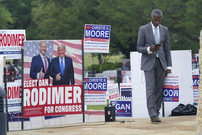 Volunteer Al Green looks at his phone as he takes a break from holding a sign supporting his candidate in a local election outside an early voting location Tuesday, April 27, 2021, in Mansfield, Texas. (AP Photo/LM Otero)