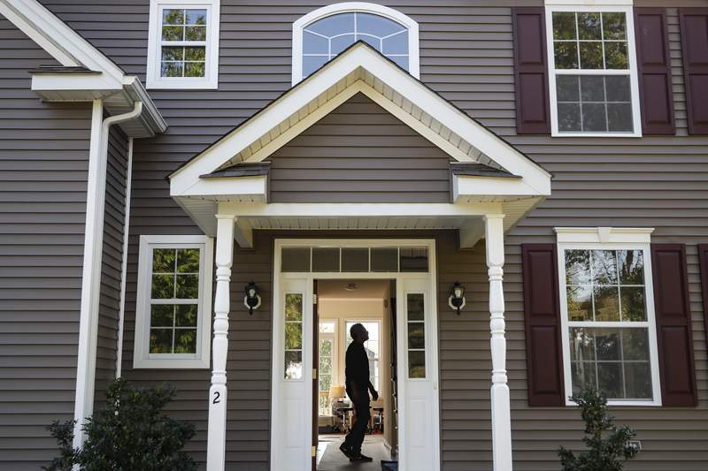 FILE - In this July 21, 2020, file photo, a homeowner tours his new home, in Washingtonville, N.Y. U.S. average rates on long-term mortgages fell this week amid signs that the halting economic recovery slowed over the summer. The key 30-year mortgage again marked an all-time low. Mortgage buyer Freddie Mac reports that the average rate on the 30-year home loan declined to 2.86% from 2.93% last week. (AP Photo/John Minchillo, File)