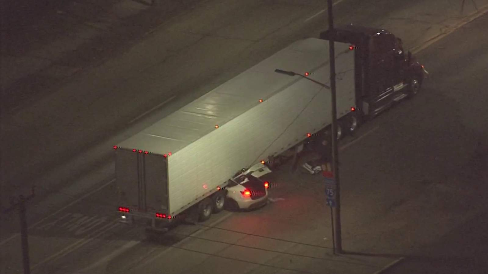 Woman in critical condition after car gets wedged under semi truck in Detroit