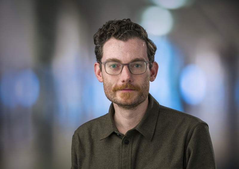 In this Feb. 7, 2019 photo provided by the Fred Hutch News Service, Trevor Bedford, a computational biologist at the Fred Hutchinson Cancer Research Center, poses at the center in Seattle. Bedford is among a group of scientists who are contributing data to the decision-making in Washington state with regards to containing the new coronavirus outbreak. (Robert Hood/Fred Hutch News Service via AP)
