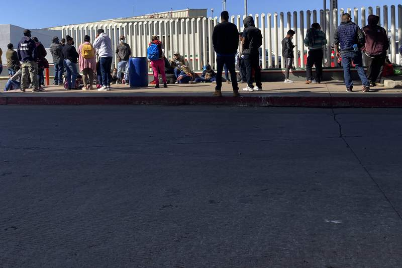 FILE - Migrants waiting to cross into the United States wait for news at the border crossing Wednesday, Feb. 17, 2021, in Tijuana, Mexico.  A federal appellate court refused late Thursday, Aug. 19 to delay implementation of a judges order reinstating a Trump administration policy forcing thousands to wait in Mexico while seeking asylum in the U.S. President Joe Biden had suspended former President Donald Trumps Remain in Mexico policy on his first day in office and the Department of Homeland Security said it was permanently terminating the program in June, according to the court record.  (AP Photo/Elliot Spagat)