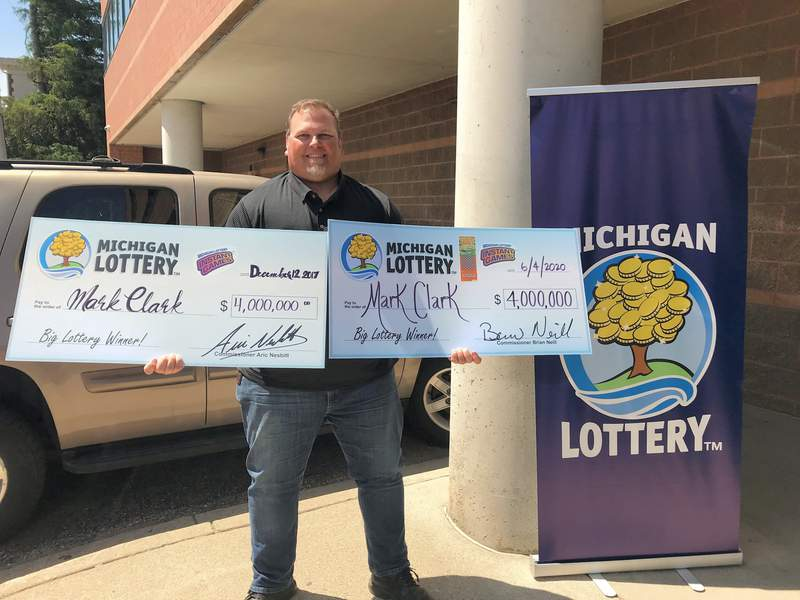 Clark displays both of his $4 million checks.