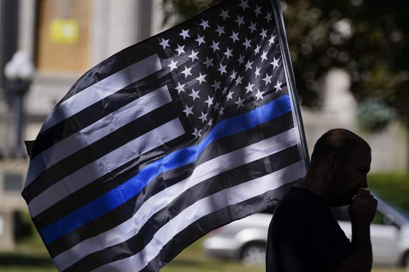 FILE - In this Aug. 30, 2020 file photo, an unidentified man participates in a Blue Lives Matter rally in Kenosha, Wis. University of Wisconsin-Madisons police chief has banned officers from using Thin Blue Line imagery while on duty. The move by Chief Kristen Roman follows criticism on social media of a Thin Blue Line flag displayed at the police departments office.  (AP Photo/Morry Gash, File)