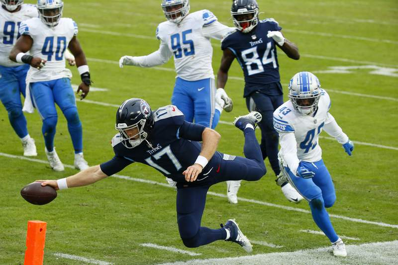 Quarterback Ryan Tannehill #17 of the Tennessee Titans dives into the end zone for a touchdown over strong safety Duron Harmon #26 of the Detroit Lions during the second quarter of the game at Nissan Stadium on December 20, 2020 in Nashville, Tennessee.