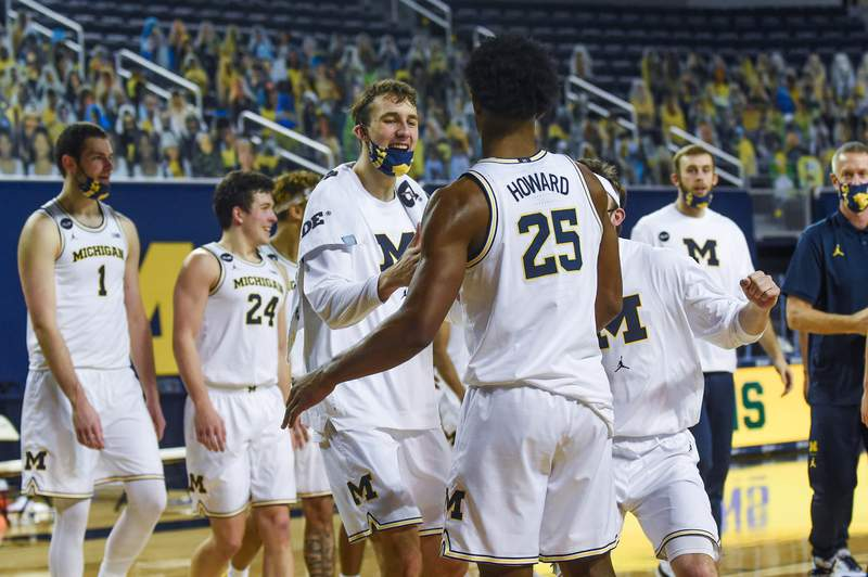 Franz Wagner #21 and Jace Howard #25 of the Michigan Wolverines celebrate after winning a college basketball game against the Northwestern Wildcats at Crisler Arena on January 3, 2021 in Ann Arbor, Michigan. The Michigan Wolverines won the game 85-66.