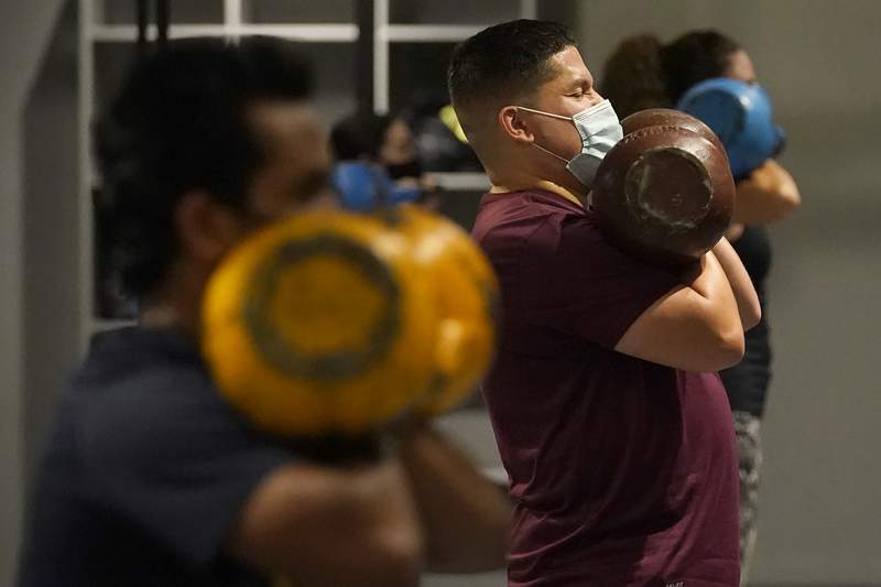FILE - In this Nov. 24, 2020, file photo, Juan Avellan, center, and others wear masks while working out in an indoor class at a Hit Fit SF gym amid the coronavirus outbreak in San Francisco. (AP Photo/Jeff Chiu, File)