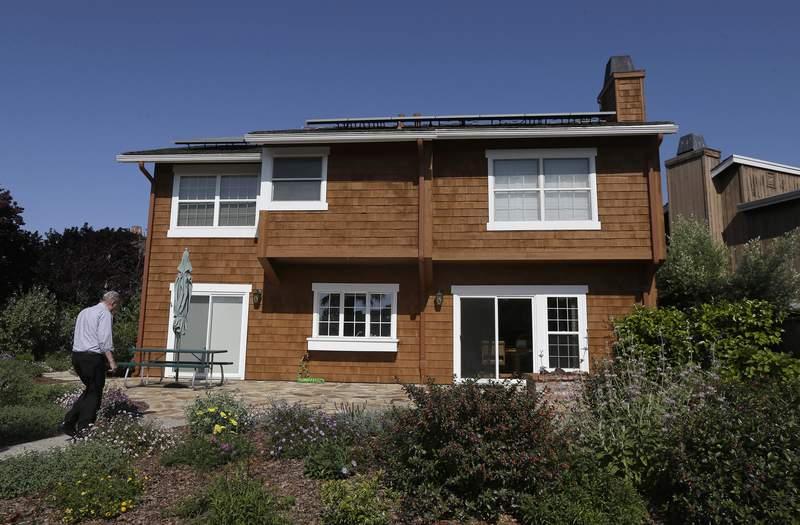 FILE - David Cunningham walks toward his solar panel-topped home, on April 20, 2015, in Foster City, Calif. With prices surging worldwide for heating oil, natural gas and other fuels, the U.S. government said Wednesday, Oct. 13, 2021,  it expects households to see jumps of up to 54% for their heating bills compared to last winter. (AP Photo/Jeff Chiu, File)