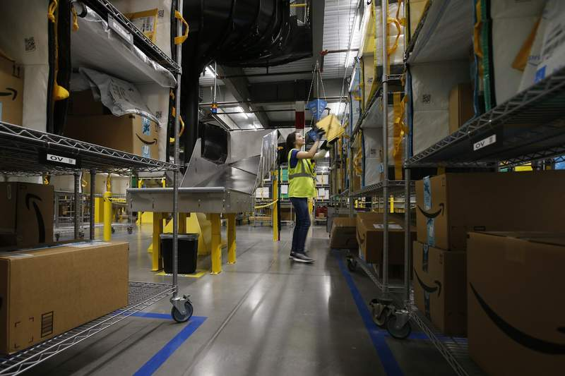 FILE - In this Dec. 17, 2019, file photo Jocelyn Nieto stows packages into special containers after Amazon robots deliver separated packages by zip code at an Amazon warehouse facility in Goodyear, Ariz. (AP Photo/Ross D. Franklin, File)