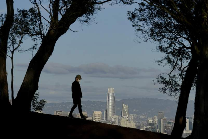 FILE - In this Dec. 17, 2020, file photo, a person wearing a face mask walks atop Tank Hill in front of the skyline during the coronavirus pandemic in San Francisco. (AP Photo/Jeff Chiu, File)