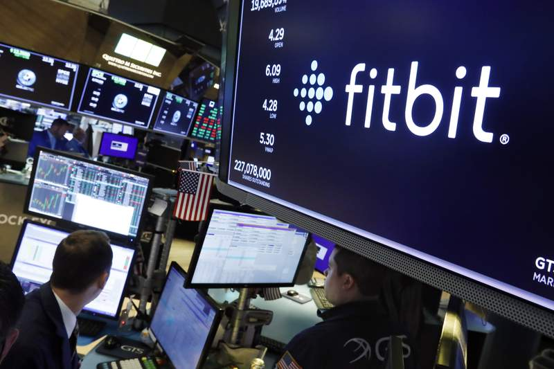 FILE - In this Oct. 28, 2019 file photo, the logo for fItbit appears above a trading post on the floor of the New York Stock Exchange.  Google has completed its $2.1 billion acquisition of fitness-gadget maker Fitbit. It's a deal that could help the internet company grow even stronger while U.S. government regulators pursue an antitrust case aimed at undermining its power. Thursday, Jan. 14, 2021 completion of the acquisition comes 14 months after Google announced a deal that immediately raised privacy alarms.   (AP Photo/Richard Drew, File)