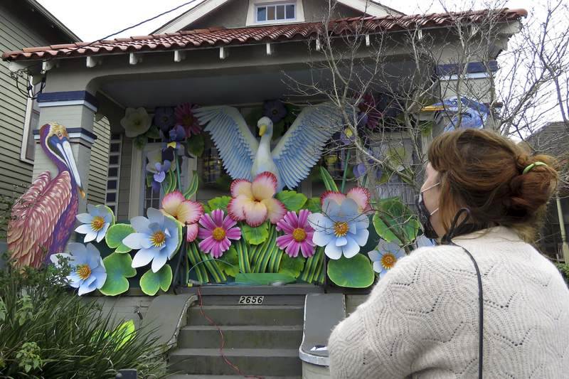 Designer, Caroline Thomas looks at a house decorated like a parade float in New Orleans on Friday, Jan. 8, 2021. All around the city, thousands of houses are being decorated as floats because the coronavirus pandemic has canceled parades that usually take place on Mardi Gras. (AP Photo/Janet McConnaughey)