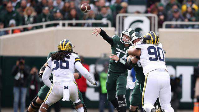 Brian Lewerke #14 of the Michigan State Spartans throws a first quarter pass while playing the Michigan Wolverines at Spartan Stadium on October 20, 2018 in East Lansing, Michigan. (Photo by Gregory Shamus/Getty Images)