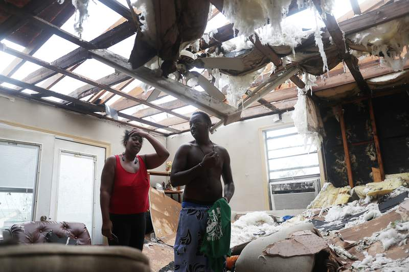Latasha Myles and Howard Anderson stand in their living room where they were sitting when the roof blew off around 2:30 a.m. as Hurricane Laura passed through the area in Lake Charles, Louisiana. (Photo by Joe Raedle/Getty Images)