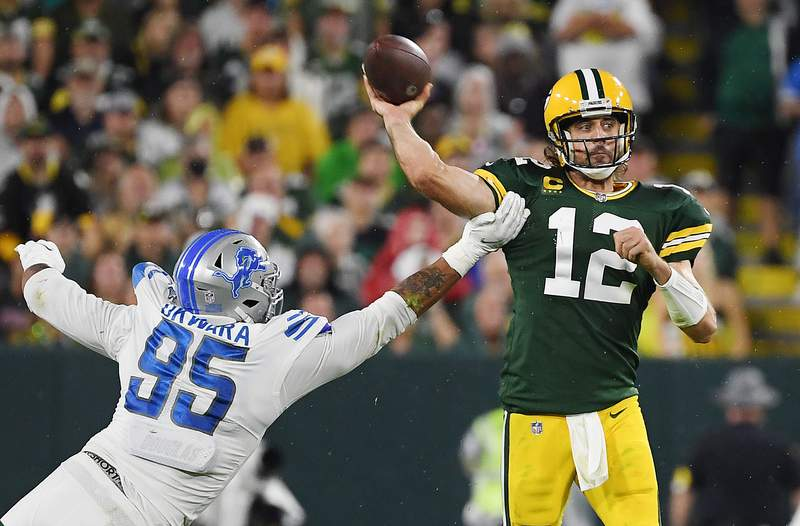 GREEN BAY, WISCONSIN - SEPTEMBER 20: Aaron Rodgers #12 of the Green Bay Packers is pressured by Romeo Okwara #95 of the Detroit Lions during the second half at Lambeau Field on September 20, 2021 in Green Bay, Wisconsin. (Photo by Quinn Harris/Getty Images)