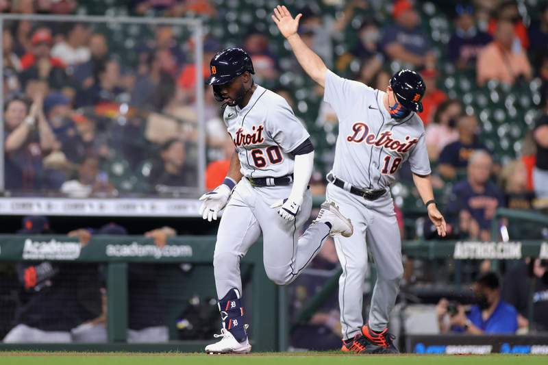 Akil Baddoo #60 of the Detroit Tigers rounds third and third base coach Chip Hale #18 after hitting a solo home run during the third inning against the Houston Astros at Minute Maid Park on April 13, 2021 in Houston, Texas.
