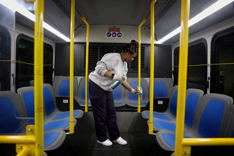 Stacy Loggins, a janitorial supervisor for Metro, wipes down the interior of a bus with disinfectant Thursday, March, 12, 2020, at a Metro facility in St. Louis. (Christian Gooden/St. Louis Post-Dispatch via AP)