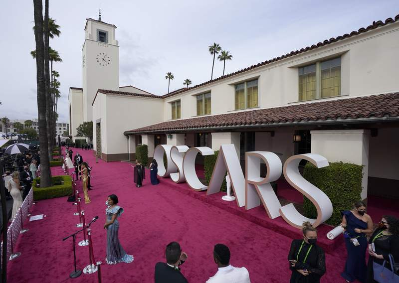 Maria Bakalova, from left, Andra Day and Regina King are interviewed and Marlee Matlin walks the red carpet at the Oscars on Sunday, April 25, 2021, at Union Station in Los Angeles. (AP Photo/Mark Terrill, Pool)
