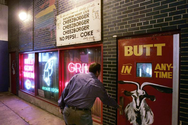 FILE - In this Sept. 23, 2005 file photo, a customer enters the Billy Goat Tavern under Chicago's Michigan Ave.  The once-busy diner tucked below a Michigan Avenue overpass in Chicago famously inspired a Saturday Night Live skit starring John Belushi and Bill Murray as short-order cooks. But the money the Billy Goat Tavern is losing now due to state-imposed business closures during the coronavirus outbreak is no joke. (AP Photo/Charles Rex Arbogast, File)