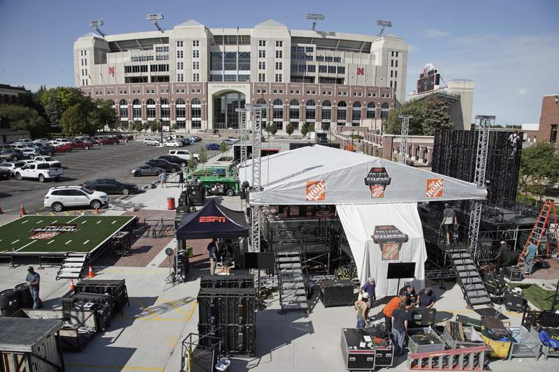 """FILE - In this Sept. 26, 2019, file photo, workers set up the ESPN """"College GameDay"""" stage in front of Memorial Stadium in Lincoln, Neb. The COVID-19 pandemic has put fall college football Saturdays in peril, but if the season can be salvaged so to will the sport's most popular pregame show. (AP Photo/Nati Harnik, File)"""