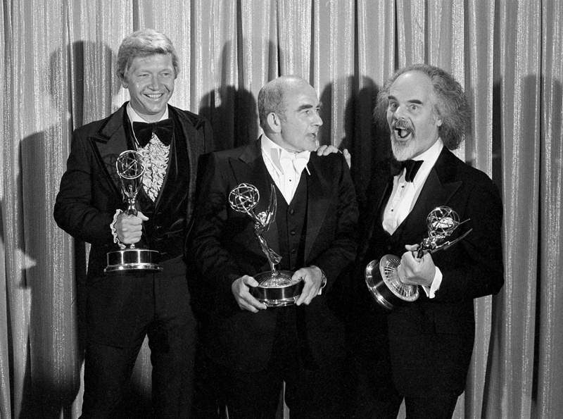 FILE - In this Sunday, Sept. 11, 1977 file photo, Screenwriter William Blinn, left, Ed Asner, center, and David Greene pose with their Emmy statuettes at the annual Primetime Emmy Awards presentation in Los Angeles. William Blinn, a screenwriter for the landmark TV projects Brians Song, Roots and the Prince film Purple Rain, has died, Thursday, Oct. 22, 2020. He was 83. (AP Photo/File)