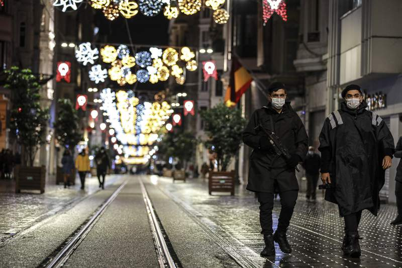 Police officers patrol Istiklal street, the main shopping street in Istanbul, minutes into the lockdown, part of the new measures to try curb the spread of the coronavirus, Saturday, Nov. 21, 2020.Turkey's President Recep Tayyip Erdogan announced a series of restrictions, including partial weekend lockdowns, to help the country grapple with the resurgence of the pandemic. Restaurants and cafes are closed and will only be allowed to serve take-away food. People won't be able to venture out of their homes after 8:00 p.m. on weekends. The restrictions also limit the hours that shops, markets and hairdressers can operate. (AP Photo/Emrah Gurel)