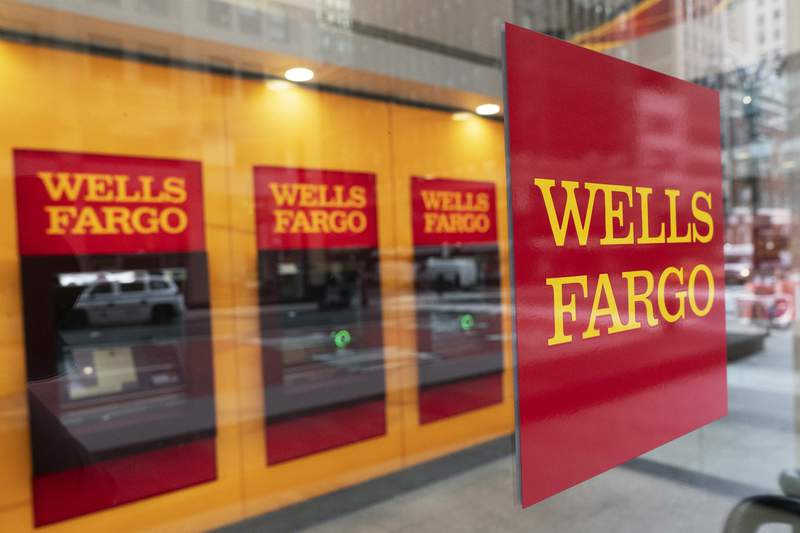 A Wells Fargo office is shown, Wednesday, Jan. 13, 2021 in New York.  Wells Fargo & Co. says its profit rose 4% to $2.99 billion in the fourth quarter of 2020. The bank, based in San Francisco, said Friday that it had earnings of 64 cents per share, compared with earnings of 60 cents a year earlier. (AP Photo/Mark Lennihan)