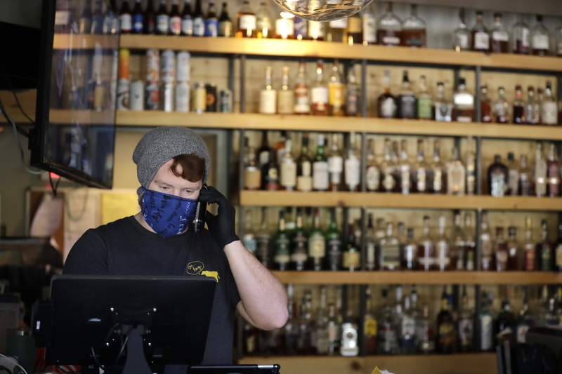 John Randall, general manager at Salt + Smoke restaurant, wears a mask and gloves as he takes an order over the phone Friday, April 10, 2020, in St. Louis. Many restaurants like Salt + Smoke have started selling groceries and other provisions as a way to help make up for revenue lost during the coronavirus outbreak. (AP Photo/Jeff Roberson)