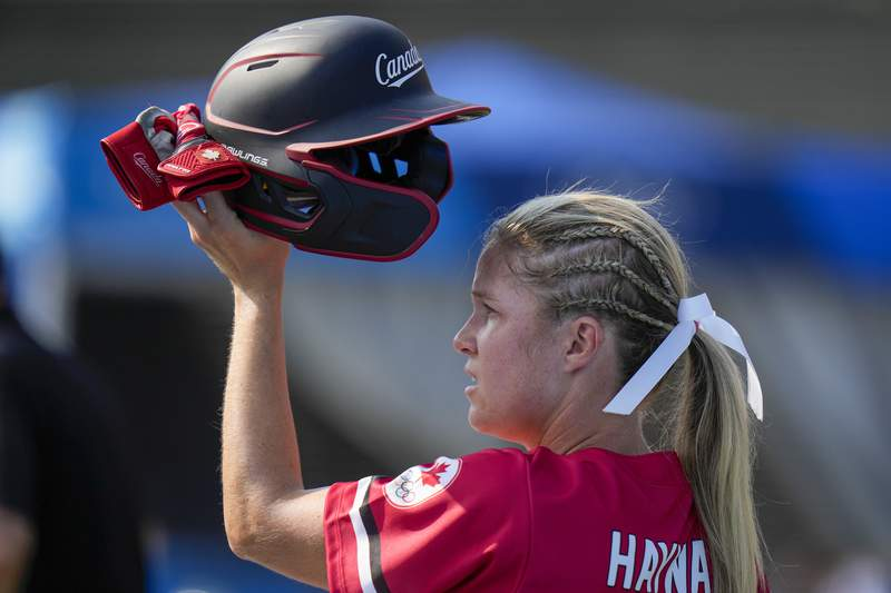 FILE - In this July 21, 2021 file photo, Canada's Victoria Hayward holds her helmet aloft during the softball game between Mexico and Canada at the 2020 Summer Olympics in Fukushima , Japan.  Hayward will be back on the field this weekend as a softball player  and as an owner. After hitting .300 at the Tokyo Olympics, the Canadian outfielder heads one of four teams that start play Saturday, Aug. 28,  at Athletes Unlimited outside Chicago.(AP Photo/Jae C. Hong, File)