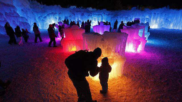 In this Saturday, Jan. 26, 2019 photo, Bruce McCafferty and his son, Dougie, pause while exploring the ice formations growing at Ice Castles in North Woodstock, N.H. (AP Photo/Robert F. Bukaty)