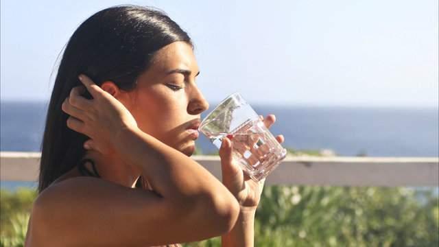 Woman drinking water (Pexels)