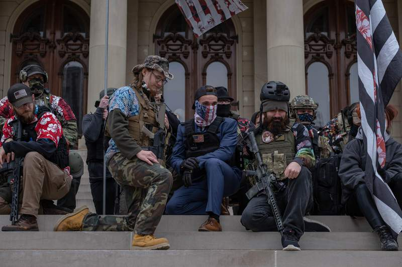 LANSING, MI - OCTOBER 17: The Boogaloo Boys kneel on the steps of the Capitol Building on October 17, 2020 during a rally in Lansing, Michigan. The Boogaloo boys called it a Unity Rally in an attempt to distance themselves from the Wolverine Watchmen who plotted to kidnap Michigans Governor Gretchen Whitmer. Two of the men arrested in the plot were affiliated with the Boogaloo Boys. (Photo by Seth Herald/Getty Images)