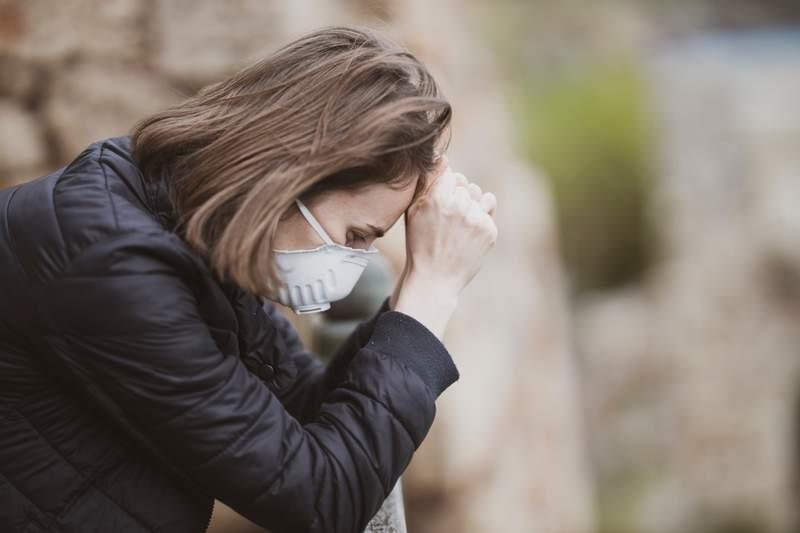 Woman wearing mask with headache