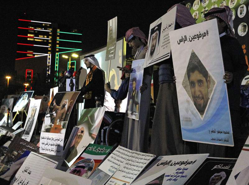 """FILE - In this Feb. 14, 2018 file photo, opposition activist Bader al-Dahoum, left, speaks amid posters that show some of those detained with a hashtag in Arabic reading, """"With Heads Held High,"""" during a protest near Kuwait's parliament in Kuwait City, Kuwait. On Sunday, March 14, 2021, Kuwaits constitutional court ordered al-Dahoum expelled from parliament citing an old conviction for insulting the late emir. The move inflamed tensions between the government and legislature, revealing the limits of political freedom in the Gulf state. (AP Photo/Jon Gambrell, File)"""