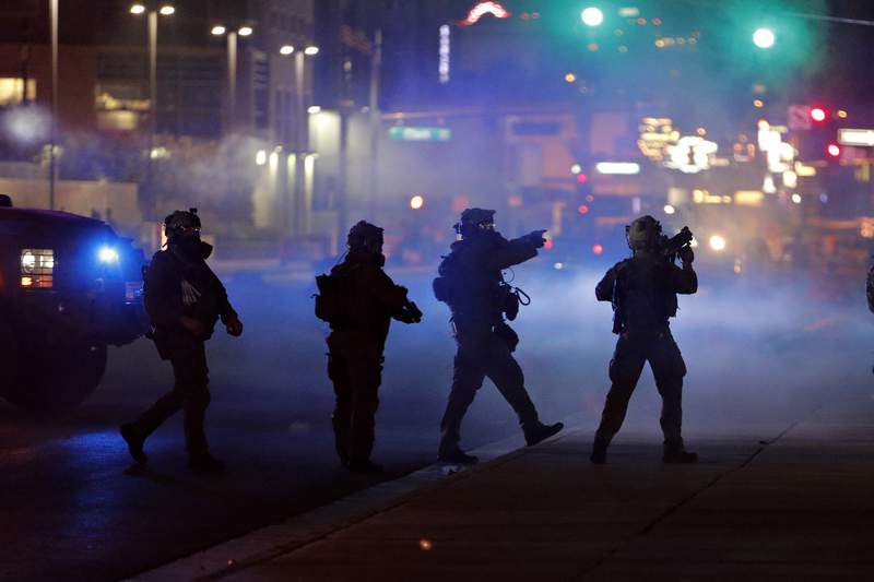 Police walk through tear gas as they try to disperse protesters Saturday, May 30, 2020, in Las Vegas, over the death of George Floyd, a black man who was in police custody in Minneapolis. Floyd died after being restrained by Minneapolis police officers on Memorial Day. (AP Photo/John Locher)