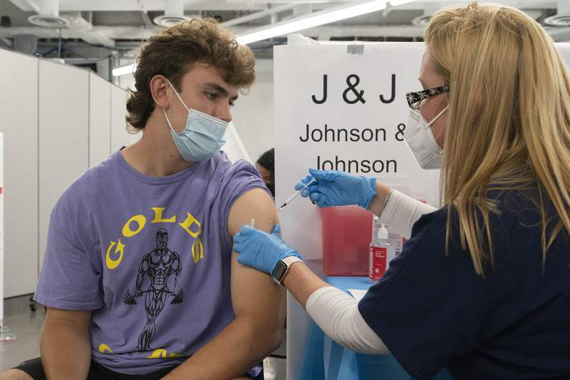 FILE — In this July 30, 2021 file photo, Bradley Sharp, of Saratoga, N.Y., gets the Johnson & Johnson vaccine from registered nurse Stephanie Wagner, in New York. Sharp needs the vaccination because it is required by his college. Hundreds of college campuses across the country have told students that they must be fully vaccinated against COVID-19 before classes begin in a matter of weeks. (AP Photo/Mark Lennihan, File)
