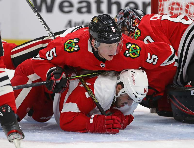 CHICAGO, ILLINOIS - JANUARY 05: Connor Murphy #5 of the Chicago Blackhawks lands on top of Robby Fabbri #14 of the Detroit Red Wings as they slide into Corey Crawford #50 at the United Center on January 05, 2020 in Chicago, Illinois. (Photo by Jonathan Daniel/Getty Images)