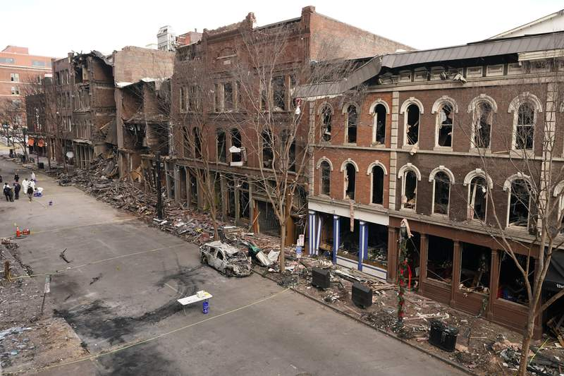 Debris remains on the sidewalks in front of buildings damaged in a Christmas Day explosion Tuesday, Dec. 29, 2020, in Nashville, Tenn. Officials have named 63-year-old Anthony Quinn Warner as the man behind the bombing in which he was killed, but the motive has remained elusive. (AP Photo/Mark Humphrey)
