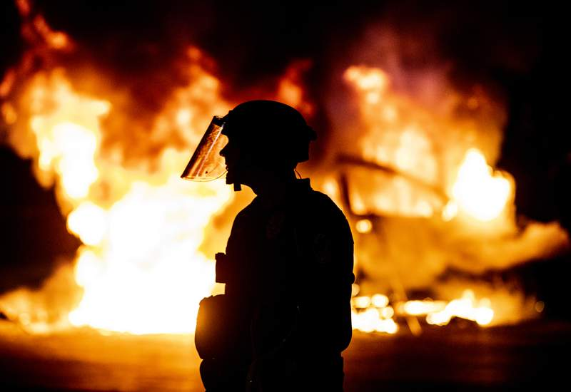 Police stands guard as Austin Fire Department put out a car fire under Interstate 35 freeway in Austin Texas, Saturday, May 30, 2020 during a protest over the death of George Floyd, a handcuffed black man who died in Minneapolis police custody on May 25. (Ricardo B. Brazziell/Austin American-Statesman via AP)